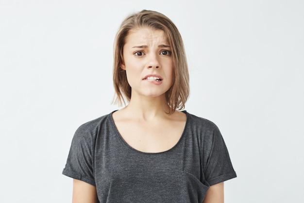 Menina bonita jovem descontente vergonha mordendo o lábio.