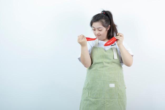 Menina bonita jovem em pé no avental xadrez e segurando duas red hot chili peppers.