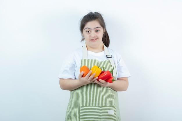 Menina bonita jovem em pé no avental xadrez e segurando legumes.