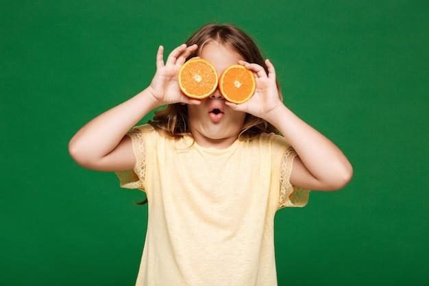 Menina bonita jovem, escondendo os olhos com laranjas sobre parede verde