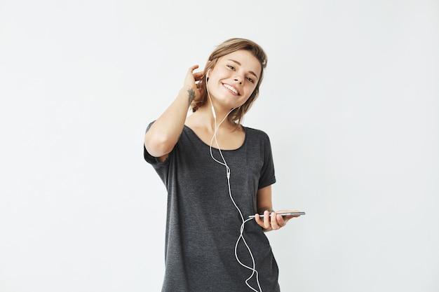 Menina bonita jovem feliz em fones de ouvido, segurando o telefone sorrindo.