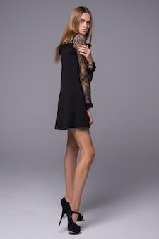 Menina bonita jovem figura fina, vestida com vestido de seda preto