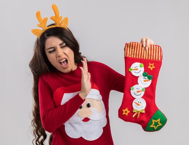 Menina bonita jovem irritada usando tiara de chifres de rena e suéter de papai noel segurando e olhando para a meia de natal, fazendo gesto de recusa isolado na parede branca