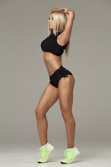Menina bonita jovem modelo de aptidão atlética posando no estúdio em um fundo cinza
