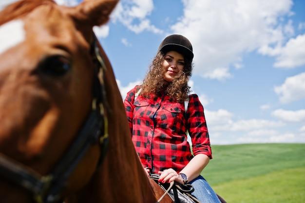 Menina bonita jovem, montando um cavalo em um campo em dia de sol.