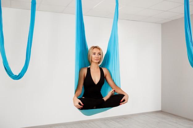 Menina bonita jovem praticando ioga aérea no ginásio.