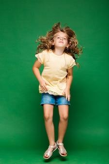 Menina bonita jovem pulando parede verde
