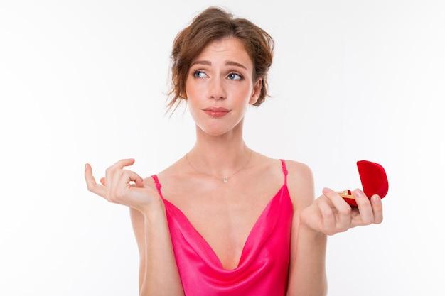 Menina bonita jovem segura uma caixa para um anel de noivado e pensa isolado no branco