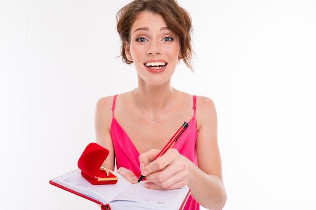 Menina bonita jovem segura uma caixa para um anel de noivado e planejamento de casamento isolado no branco