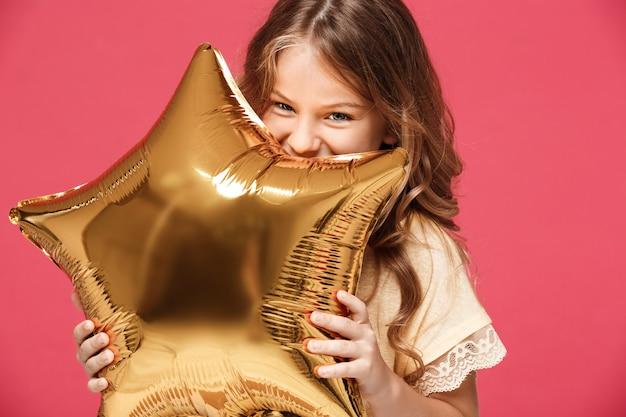 Menina bonita jovem segurando balão e sorrindo sobre parede rosa