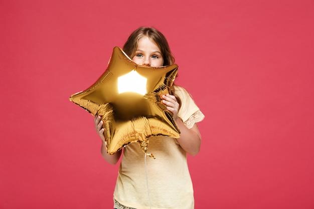 Menina bonita jovem segurando balão sobre parede rosa