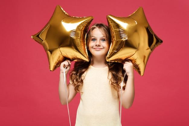 Menina bonita jovem segurando balões e sorrindo sobre parede rosa