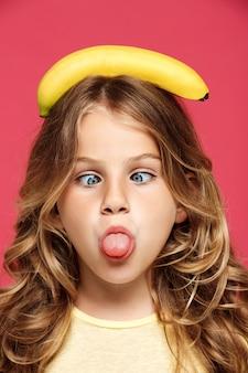 Menina bonita jovem segurando banana na cabeça sobre parede rosa