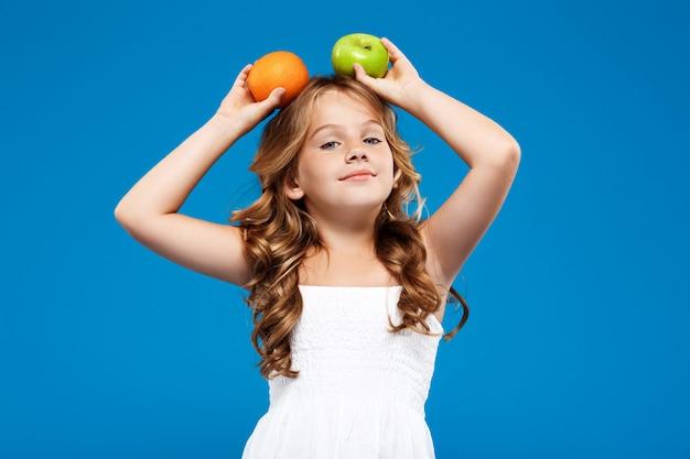 Menina bonita jovem segurando maçã e laranja sobre parede azul