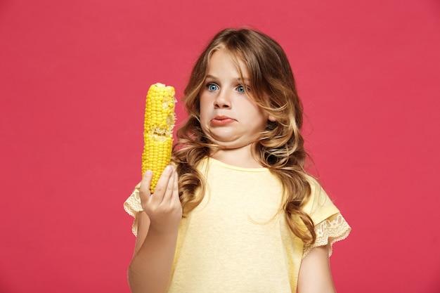 Menina bonita jovem segurando milho sobre parede rosa
