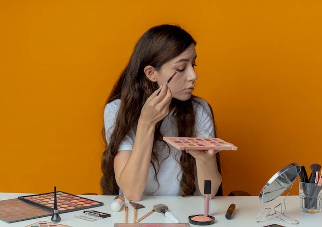 Menina bonita jovem sentada à mesa de maquiagem com ferramentas de maquiagem, olhando para o espelho, segurando a paleta de sombras e aplicando a sombra com pincel isolado em fundo laranja