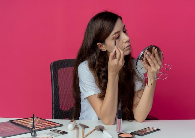 Menina bonita jovem sentada à mesa de maquiagem com ferramentas de maquiagem segurando e olhando para o espelho e modelando as sobrancelhas com pincel de sobrancelha isolado no fundo carmesim
