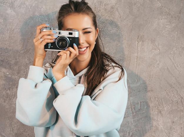 Menina bonita jovem sorridente fotógrafo tirando fotos usando sua câmera retro. mulher fazendo fotos.