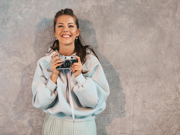 Menina bonita jovem sorridente fotógrafo tirando fotos usando sua câmera retro.