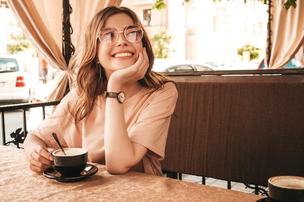 Menina bonita jovem sorridente hipster em roupas da moda no verão. mulher despreocupada, sentado no terraço varanda café e bebendo café. modelo positivo, se divertindo e sonhos