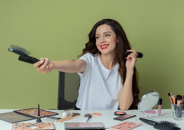 Menina bonita jovem sorridente sentada à mesa de maquiagem com ferramentas de maquiagem segurando e esticando os pentes e olhando para o lado isolado no fundo verde oliva