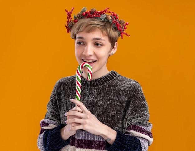 Menina bonita jovem vestindo uma coroa de flores de natal segurando uma bengala de natal olhando para o lado se preparando para comê-la isolada em um fundo laranja
