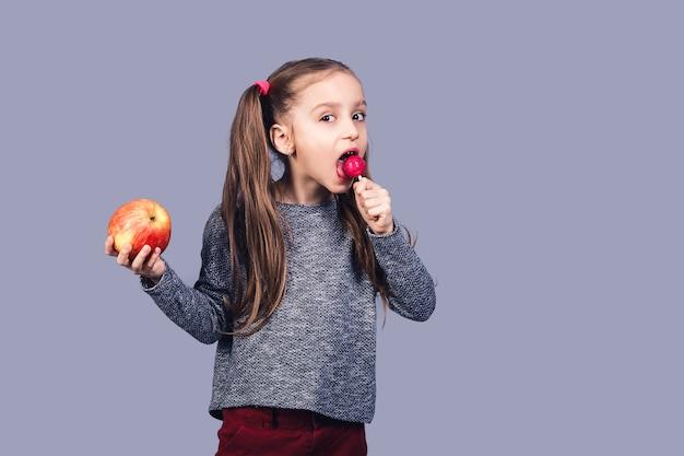 Menina bonita lambe um pirulito e segura uma maçã. o conceito de escolher entre alimentos saudáveis e não saudáveis. isolado na superfície cinza