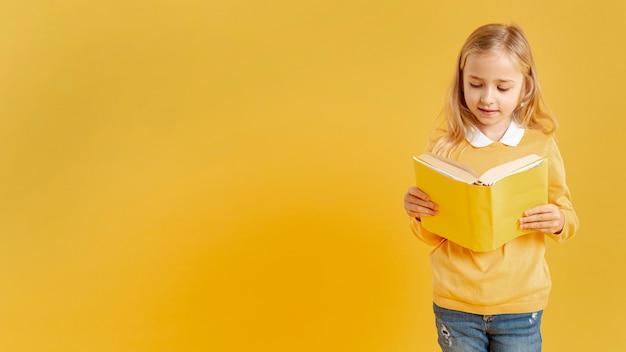 Menina bonita lendo com cópia-espaço