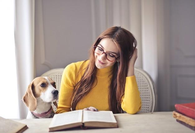 Menina bonita lendo com seu cachorro