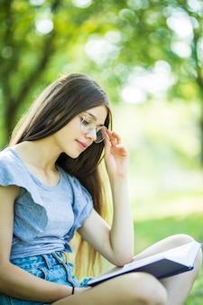 Menina bonita lendo livro no parque na luz do sol de verão
