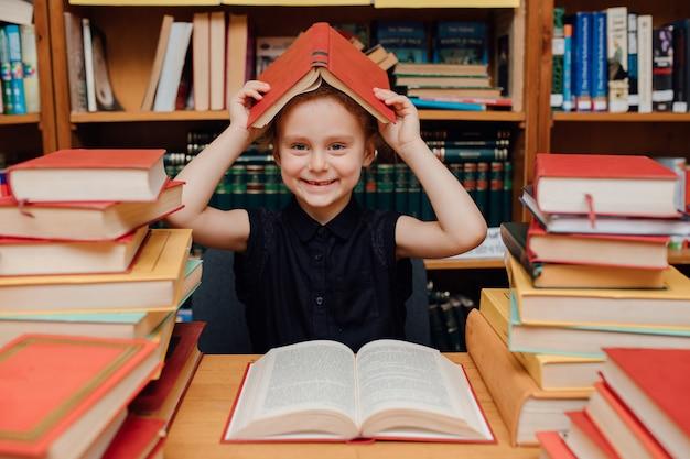 Menina bonita lendo na biblioteca