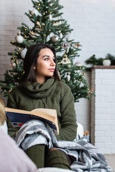 Menina bonita lendo um livro em uma atmosfera de natal