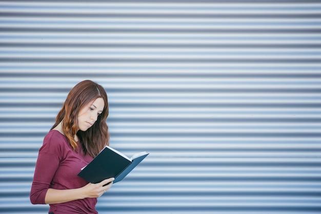 Menina bonita, lendo um livro na rua em frente à parede de metal