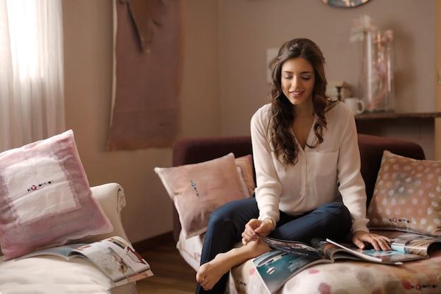 Menina bonita, lendo uma revista em casa