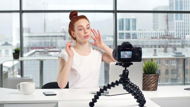 Menina bonita leva um tutorial de beleza em uma câmera de vídeo digital