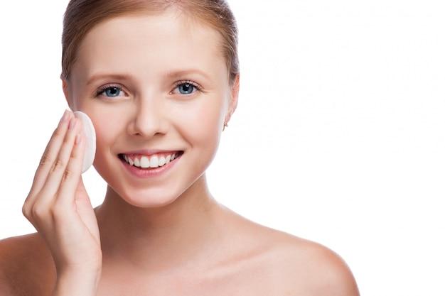 Menina bonita limpa a maquiagem dos olhos