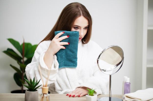 Menina bonita limpa o rosto com uma toalha em casa na frente de um espelho