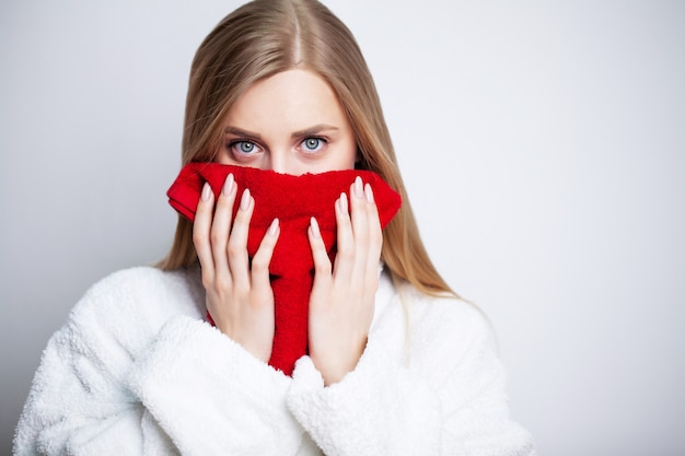 Menina bonita limpa o rosto com uma toalha em casa