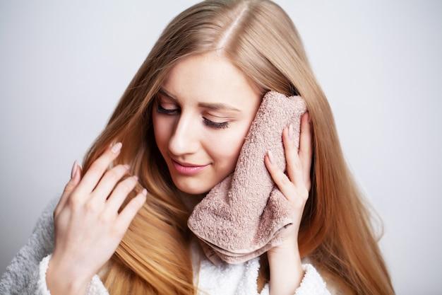 Menina bonita limpa o rosto com uma toalha