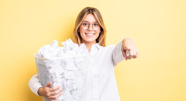 Menina bonita loira apontando para a câmera escolhendo você. conceito de lixo de bolas de papel