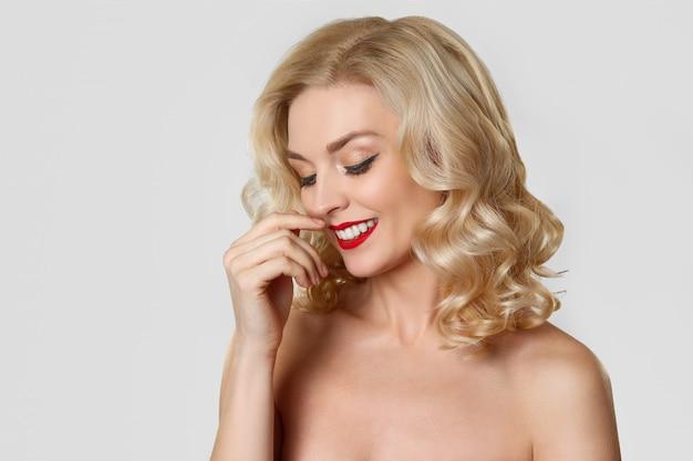 Menina bonita loira com maquiagem de olho de gato e lábios vermelhos, tocando seu cabelo ondulado
