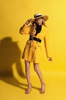 Menina bonita loira com sardas em roupa amarela e chapéu de palha no fundo amarelo