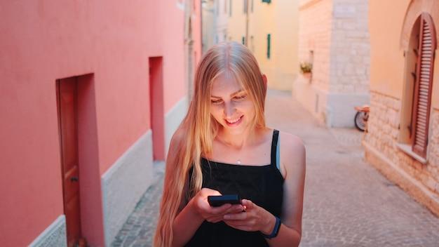 Menina bonita loira conversando no smartphone enquanto caminha pela rua da cidade velha sorrindo e ...