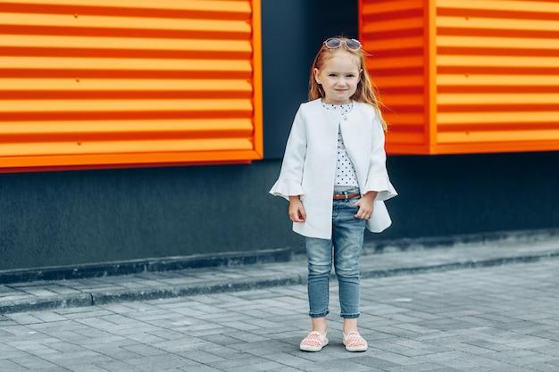 Menina bonita loira de jaleco branco e calças de ganga