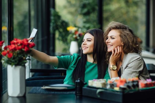 Menina bonita loira e morena tirando uma foto ao telefone celular com prato de sushi na mesa. chenese coma, amigos.