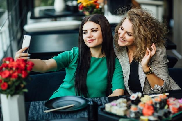Menina bonita loira e morena tirando uma foto ao telefone celular com prato de sushi na mesa. chenese comer, hora de amigos.