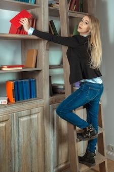Menina bonita loira em pé em uma escada de madeira na biblioteca ao lado de prateleiras com livros, pega o livro e olha para a câmera