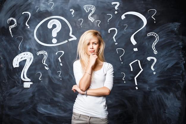 Menina bonita loira em uma camiseta branca faz uma pergunta sobre um fundo preto. mulher pensa com pontos de interrogação no quadro de giz.