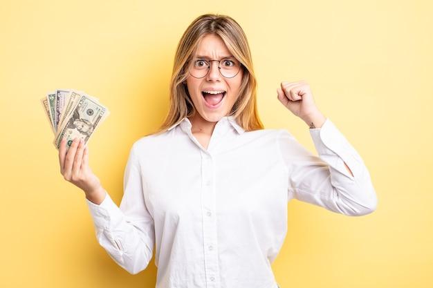 Menina bonita loira gritando agressivamente com uma expressão de raiva. conceito de notas de dólar