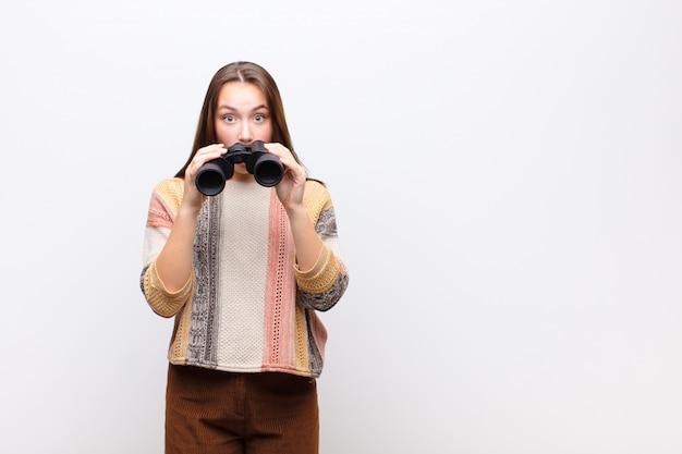 Menina bonita loira jovem segurando um binóculo contra parede branca